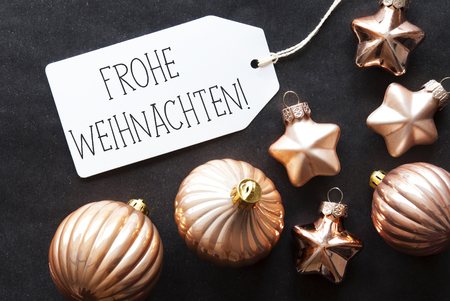 weihnachten: Label With German Text Frohe Weihnachten Means Merry Christmas. Bronze Christmas Tree Balls On Black Paper Background. Christmas Decoration Or Texture. Flat Lay View