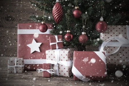 nostalgic christmas: Nostalgic Christmas Tree With Gifts Or Presents In The Front Of Wooden Background. White Ribbon With Bow. Rustic Or Retro Style. Christmas Decoration Like Balls And Snowflakes