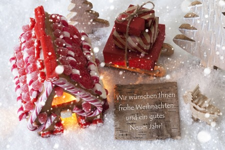 weihnachten: Label With German Text Wir Wuenschen Frohe Weihnachten Und Ein Gutes Neues Jahr Means Merry Christmas And Happy New Year. Gingerbread House On Snow. Decoration Like Sleigh With Gifts And Snowflakes
