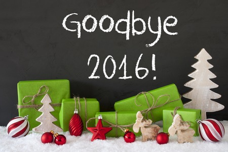English Text Goodbye 2016 For Happy New Year. Green Gifts Or Presents With Christmas Decoration Like Tree, Moose Or Red Christmas Tree Ball. Black Cement Wall As Background With Snow. Stock Photo