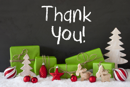 English Text Thank You. Green Gifts Or Presents With Christmas Decoration Like Tree, Moose Or Red Christmas Tree Ball. Black Cement Wall As Background With Snow. Stock Photo