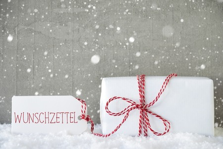 wish  list: One Christmas Present On Snow. Cement Wall As Background With Snowflakes. Modern And Urban Style. Card For Birthday Or Seasons Greetings. Label With German Text Wunschzettel Means Wish List