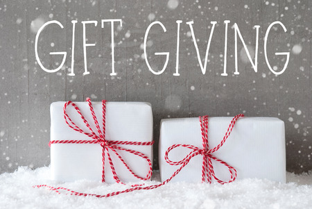 English Text Gift Giving. Two White Christmas Gifts Or Presents On Snow. Cement Wall As Background With Snowflakes. Modern And Urban Style. Card For Birthday Or Seasons Greetings.