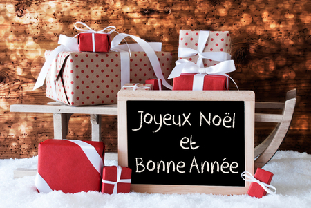 bonne: Chalkboard With FrenchText Joyeux Noel Et Bonne Annee Means Merry Christmas And Happy New Year. Sled With Christmas And Winter Decoration. Presents On Snow With Wooden Background And Bokeh Effect. Stock Photo