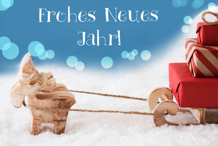 Moose Is Drawing A Sled With Red Gifts Or Presents In Snow. Christmas Card For Seasons Greetings. Light Blue Background With Bokeh Effect. German Text Frohes Neues Jahr Means Happy New Year