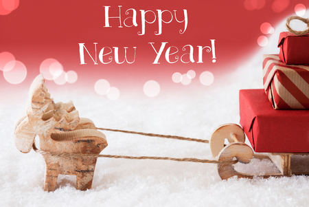 christmassy: Moose Is Drawing A Sled With Red Gifts Or Presents In Snow. Christmas Card For Seasons Greetings. Red Christmassy Background With Bokeh Effect. English Text Happy New Year