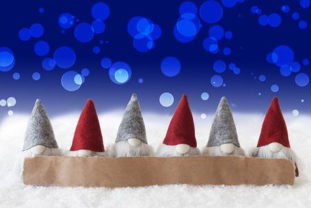 gnomos: Etiquetar con copia espacio para Publicidad. Tarjeta de felicitación de Navidad con gnomos. Espumoso bokeh y fondo azul con nieve Foto de archivo