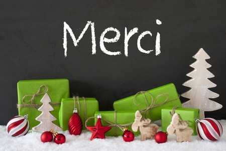 merci: French Text Merci Means Thank You. Green Gifts Or Presents With Christmas Decoration Like Tree, Moose Or Red Christmas Tree Ball. Black Cement Wall As Background With Snow.
