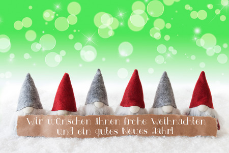 Label With German Text Wir Wuenschen Frohe Weihnachten Und Ein Gutes Neuse Jahr Means Merry Christmas And Happy New Year. Card With Gnomes. Sparkling Bokeh And Green Background With Snow And Stars. Stock Photo