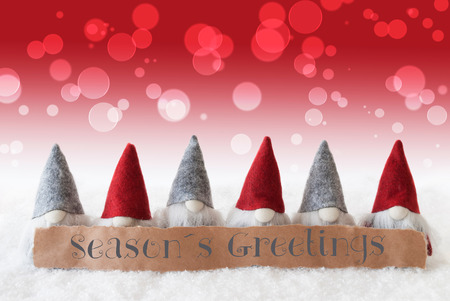 christmassy: Label With English Text Seasons Greetings. Christmas Greeting Card With Red Gnomes. Bokeh And Christmassy Background With Snow.