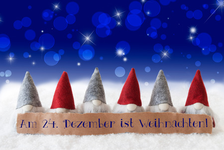weihnachten: Label With German Text Am 24. Dezember Ist Weihnachten Means December 24th Is Christmas Eve. Christmas Greeting Card With Gnomes. Sparkling Bokeh And Blue Background With Snow And Stars.