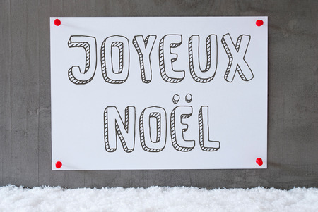 Label With French Text Joyeux Noel Means Merry Christmas. Urban And Modern Cement Wall As Background On Snow Stock Photo