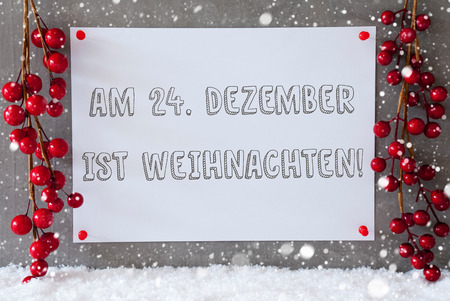 weihnachten: Label With German Text Am 24. Dezember Ist Weihnachten Means December 24th Is Christmas Eve. Red Christmas Decoration On Snow. Urban And Modern Cement Wall As Background With Snowflakes.