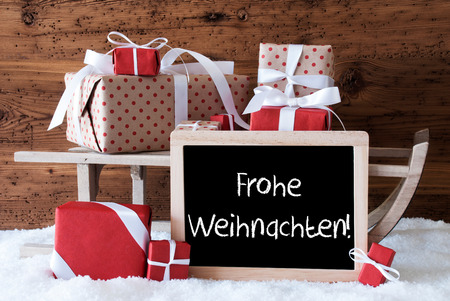 weihnachten: Chalkboard With German Text Frohe Weihnachten Means Merry Christmas. Sled With Christmas And Winter Decoration. Gifts And Presents On Snow With Wooden Background.