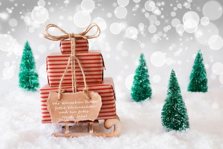 weihnachten: Label With German Text Wir Wuenschen Frohe Weihnachten Und Ein Gutes Neues Jahr Means Merry Christmas And Happy New Year. Sleigh Or Sled With Christmas Gifts Or Presents. Stock Photo