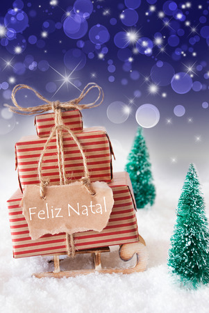 natal: Vertical Image Of Sleigh Or Sled With Christmas Gifts Or Presents. Snowy Scenery With Snow And Trees. Blue Sparkling Background With Bokeh. Label With Portuguese Text Feliz Natal Means Merry Christmas