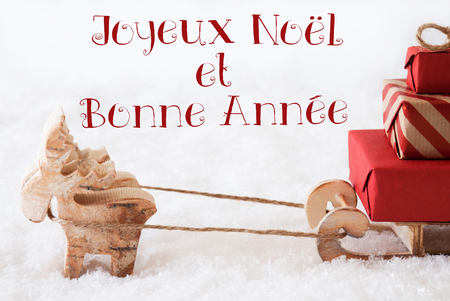 bonne: Moose Is Drawing A Sled With Red Gifts Or Presents In Snow. Christmas Card For Seasons Greetings. French Text Joyeux Noel Et Bonne Annee Means Merry Christmas And Happy New Year Stock Photo