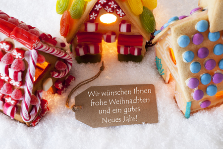 Label With German Text Wir Wuenschen Frohe Weihnachten Und Ein Gutes Neues Jahr Means Merry Christmas And Happy New Year. Colorful Gingerbread House On Snow. Christmas Card For Seasons Greetings