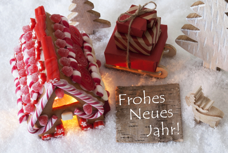 Label With German Text Frohes Neues Jahr Means Happy New Year. Gingerbread House On Snow With Christmas Decoration Like Trees And Moose. Sleigh With Christmas Gifts Or Presents.