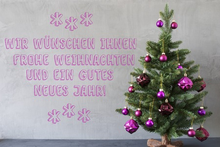 weihnachten: German Text Frohe Weihnachten Und Gutes Neues Jahr Means Merry Christmas And Happy New Year. Christmas Tree With Purple Balls. Gray Cement Or Concrete Wall For Urban, Modern Industrial Style.
