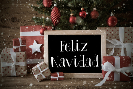 greetings card: Nostalgic Christmas Card For Seasons Greetings. Christmas Tree With Balls And Snowflakes. Gifts In The Front Of Wooden Background. Chalkboard With Spanish Text Feliz Navidad Means Merry Christmas