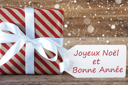 bonne: Christmas Gift Or Present On Wooden Background With Snowflakes. Card For Seasons Greetings. White Ribbon With Bow. French Text Joyeux Noel Et Bonne Annee Means Merry Christmas And A Happy New Year Stock Photo