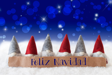 Label With Spanish Text Feliz Navidad Means Merry Christmas. Christmas Greeting Card With Gnomes. Sparkling Bokeh And Blue Background With Snow And Stars. Stock Photo