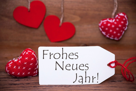 Label With German Text Frohes Neues Jahr Means Happy New Year. White Label With Red Textile Hearts. Retro Brown Wooden Background.