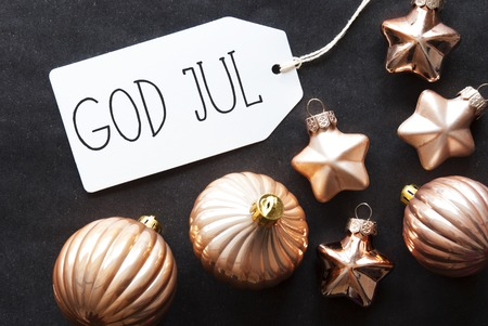 christmas ornamentation: Label With Swedish Text God Jul Means Merry Christmas. Bronze Christmas Tree Balls On Black Paper Background. Christmas Decoration Or Texture. Flat Lay View