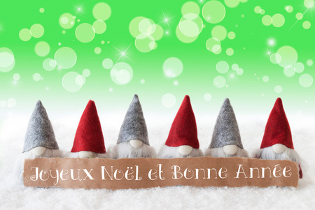 bonne: Label With French Text Joyeux Noel Et Bonne Annee Means Merry Christmas And Happy New Year. Christmas Greeting Card With Gnomes. Sparkling Bokeh And Green Background With Snow And Stars. Stock Photo