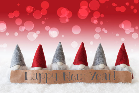 christmassy: Label With English Text Happy New Year. Christmas Greeting Card With Red Gnomes. Bokeh And Christmassy Background With Snow.
