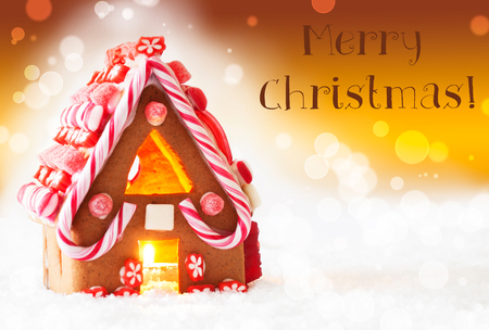 atmosphere: Gingerbread House In Snowy Scenery As Christmas Decoration. Candlelight For Romantic Atmosphere. Golden Background With Bokeh Effect. English Text Merry Christmas Stock Photo