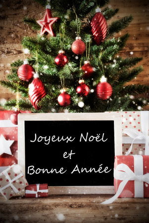 bonne: Christmas Card With Tree And Balls. Gifts Or Presents In The Front Of Wooden Background. Chalkboard With French Text With Joyeux Noel et Bonne Annee Means Merry Christmas And Happy New Year