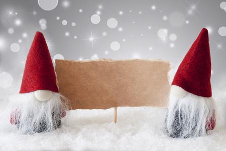 Christmas Greeting Card con due rossi Gnomi. Sparkling bokeh e Noble sfondo argento con neve. Copia spazio per la pubblicità