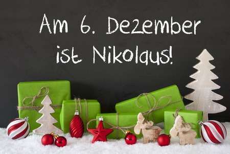 German Text Am 6. Dezember Ist Nikolaus Means December 6th Is St Nicholas Day. Green Gifts With Decoration Like Tree, Moose Or Red Christmas Tree Ball. Black Cement Wall As Background With Snow.