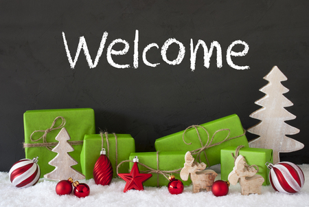 English Text Welcome. Green Gifts Or Presents With Christmas Decoration Like Tree, Moose Or Red Christmas Tree Ball. Black Cement Wall As Background With Snow. Stock Photo