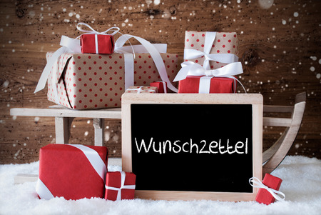 wish  list: Chalkboard With German Text Wunschzettel Means Wish List. Sled With Christmas And Winter Decoration And Snowflakes. Gifts And Presents On Snow With Wooden Background.
