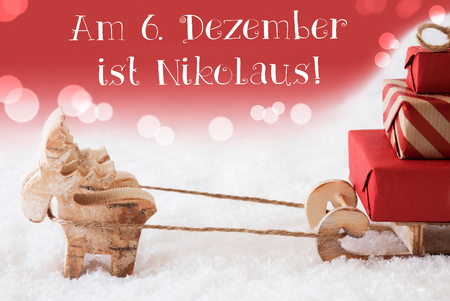 Moose Is Drawing A Sled With Red Gifts Or Presents In Snow. Christmas Card For Seasons Greetings. Red Background With Bokeh Effect. German Text Am 6. Dezember Ist Nikolaus Means Nicholas Day
