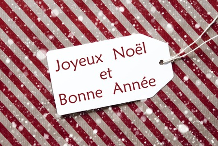 bonne: One Label On A Red And Brown Striped Wrapping Paper. Textured Background With Snowflakes. Tag With Ribbon. French Text Joyeux Noel Et Bonne Annee Means Merry Christmas And Happy New Year
