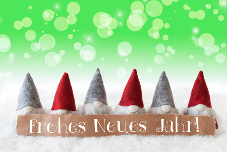 Label With German Text Frohes Neues Jahr Means Happy New Year. Christmas Greeting Card With Gnomes. Sparkling Bokeh And Green Background With Snow And Stars. Stock Photo