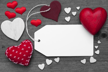 hot spot: Label With Copy Space For Advertisement. Red Textile Hearts On Wooden Gray Background. Retro Or Vintage Style. Black And White Image With Colored Hot Spot. Stock Photo