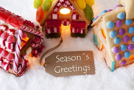 greetings card: Label With English Text Seasons Greetings. Colorful Gingerbread House On Snow. Christmas Greeting Card