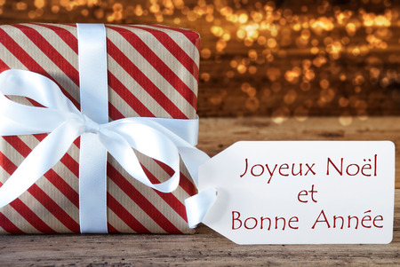bonne: Macro Of Christmas Gift Or Present On Atmospheric Wooden Background. White Ribbon With Bow. French Text Joyeux Noel Et Bonne Annee Means Merry Christmas And Happy New Year Stock Photo