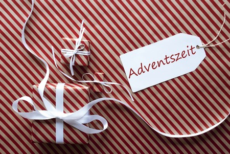advent season: Two Gifts Or Presents With White Ribbon. Red And Brown Striped Wrapping Paper. Christmas Or Greeting Card. Label With German Text Adventszeit Means Advent Season