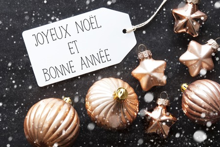 bonne: Label With French Text Joyeux Noel Et Bonne Annee Means Merry Christmas And Happy New Year. Bronze Christmas Tree Balls On Black Paper Background With Snowflakes. Flat Lay View