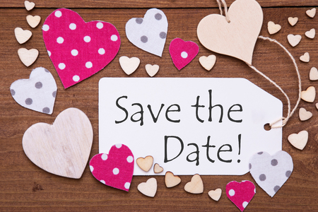 a meeting with a view to marriage: One Label With English Text Save The Date. Flat Lay View With Wooden Vintage Background. Pink Wooden And Paper Hearts.