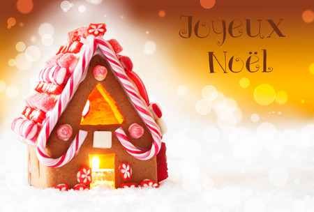 joyeux: Gingerbread House In Snowy Scenery As Christmas Decoration. Candlelight For Romantic Atmosphere. Golden Background With Bokeh Effect. French Text Joyeux Noel Means Merry Christmas Stock Photo