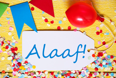 fasching: White Label With German Text Alaaf Means Happy Carnival. Close Up Of Party Decoration Like Streamer, Confetti And Balloon. Flat Lay Or Top View. Yellow Wooden Background