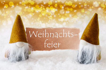 gnomos: German Text Weihnachtsfeier Means Christmas Party. Christmas Greeting Card With Two Golden Gnomes. Sparkling Bokeh And Noble Background With Snow.
