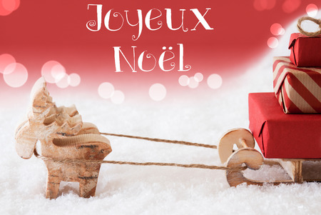 christmassy: Moose Is Drawing A Sled With Red Gifts Or Presents In Snow. Christmas Card For Seasons Greetings. Red Christmassy Background With Bokeh Effect. French Text Joyeux Noel Means Merry Christmas